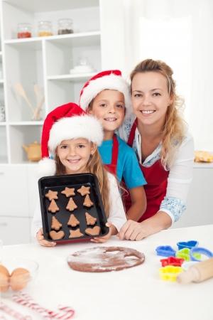 galletas de navidad: Los niños llevaban sombreros de santa haciendo galletas de la Navidad con su madre