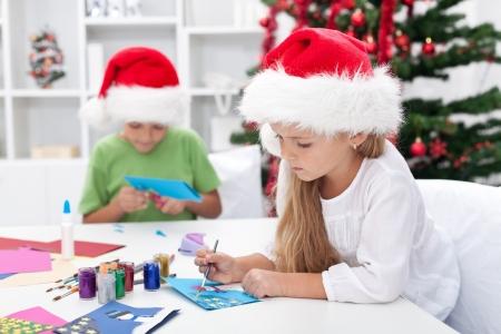 seasonal greeting: Kids making christmas or seasonal greeting cards Stock Photo
