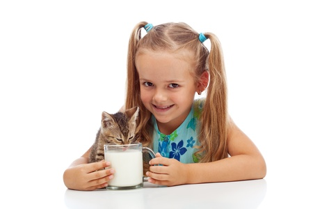 Happy little girl and her kitten sharing a cup of milk - isolated photo