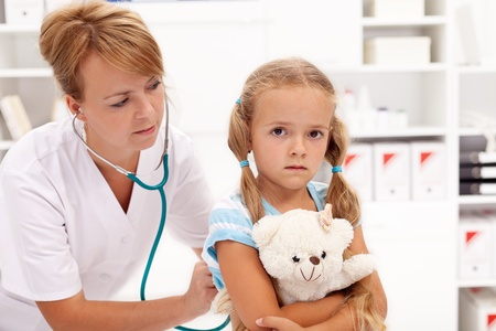 Little girl at the doctor - health professional checking her with stethoscope photo