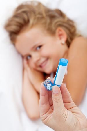 homeopatia: Niña recibiendo medicación homeopática - Mano con la botella y gránulos en primer plano Foto de archivo