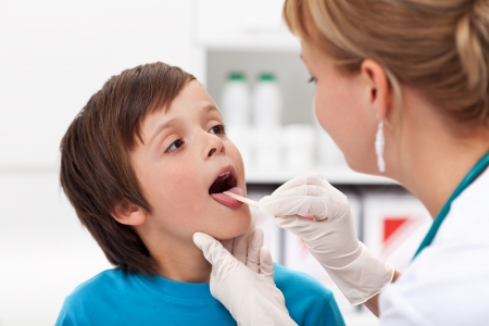 painful: Say aaah - little boy at the physician checking his throat Stock Photo