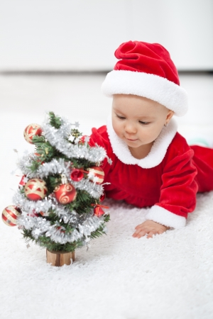 christmas baby: My first christmas - baby girl in santa outfit with small decorated tree Stock Photo
