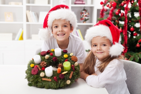 advent wreath: Kids holding an advent wreath they decorated - proud of their work Stock Photo