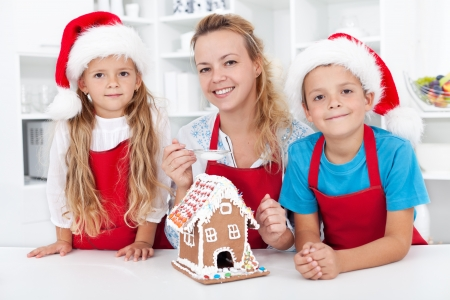 Family at christmas making a gingerbread cookie house together photo