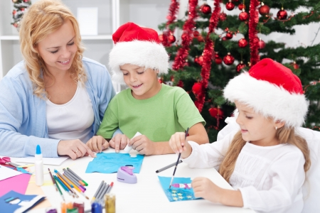 Family around christmas time making greeting cards wearing santa hats photo