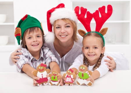 Happy woman with kids in christmas hats holding gingerbread people photo