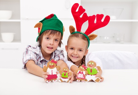 Happy christmas kids with elf and reindeer hats holding decorated gingerbread people photo