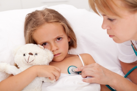 stethoscope girl: Health professional checking on sick little girl laying in bed - closeup