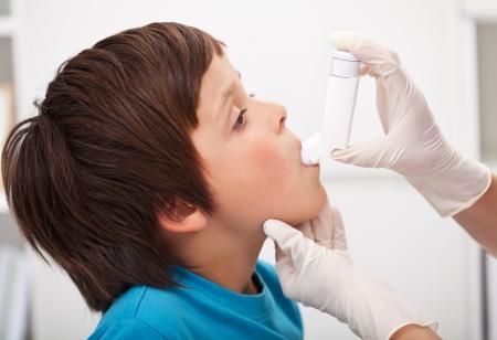 inhale: Boy with respiratory system illness receiving help using an inhaler