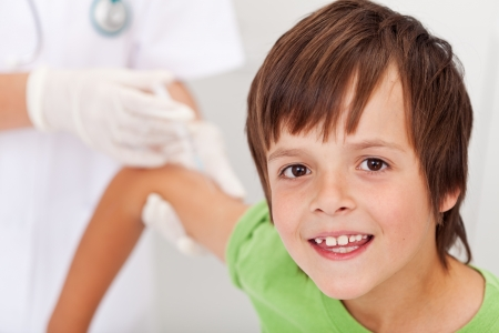 Happy boy receiving vaccine or injection - health professional in the background Stock Photo - 16469570