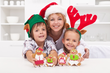 Happy woman and kids in christmas hats making gingerbread cookie family photo