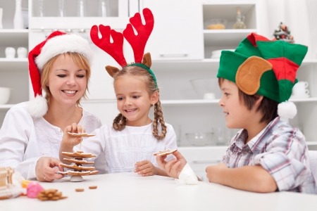 Happy family with seasonal hats making gingerbread christmas tree photo