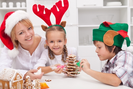 Woman with santa hat and her kids dressed as reindeer and elf decorating christmas cookies