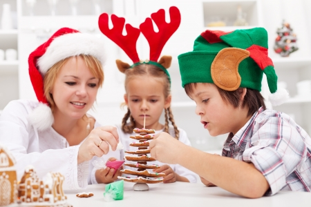 Family decorating the gingerbread christmas tree together - focus on the boy photo
