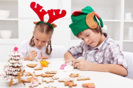 Santa little helpers - reindeer and elf - decorating gingerbread cookies at christmas time Stock Photo