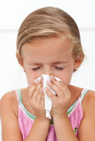 sniffle: Little girl with the flu blowing nose - closeup Stock Photo