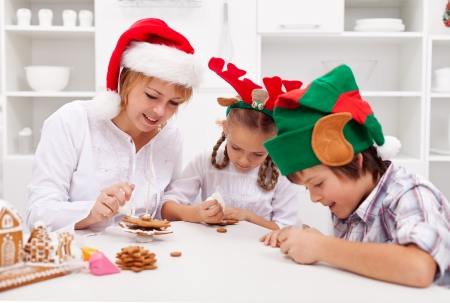 Happy christmas family decorating gingerbread cookies in the kitchen photo