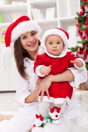 Mother and baby girl celebrating christmas together for the first time photo
