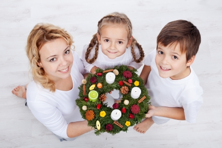 corona de adviento: Mujer con dos niños que sostienen corona de adviento - vacaciones en la familia