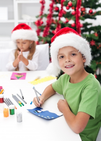 seasonal greeting: Kids making christmas and seasonal greeting cards in front of the decorated tree