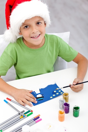Boy making christmas greeting card wearing santa hat photo