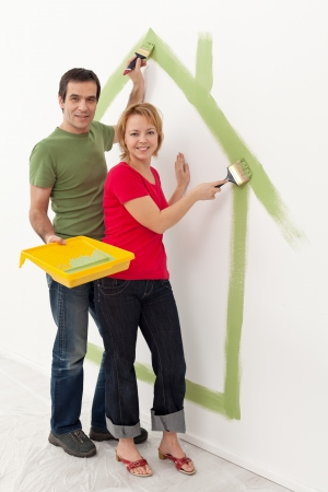 home renovations: Couple dreaming up their new home - painting it on the wall Stock Photo