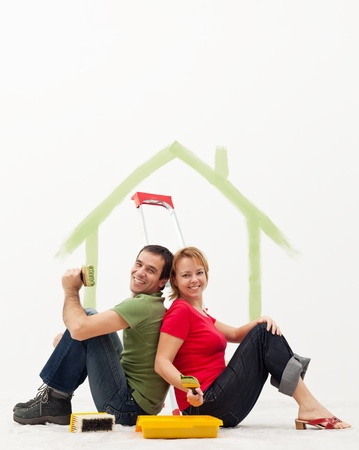 Young couple in their new home with painting utensils photo