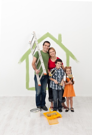 redecorating: Young family with kids redecorating their home - holding painting utensils and smiling Stock Photo