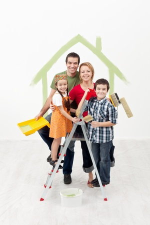 Family with kids painting their new home - smiling and holding utensils Stock Photo - 16890861