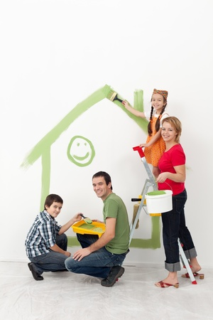 Family with kids redecorating their home - smiling with painting utensils photo