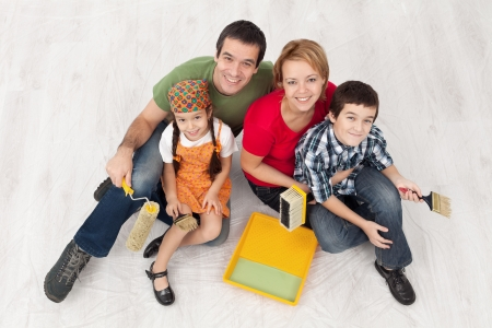 Family with two kids ready to pait their home - sitting on the protection foil, top view Stock Photo - 16890867