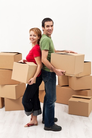 Couple moving in to a new home - carrying cardboard boxes photo