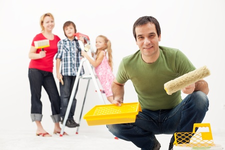 redecorating: Happy family with kids redecorating their home - painting together