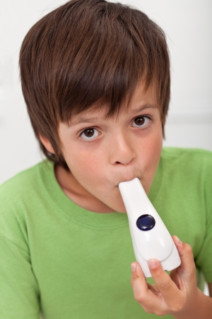 Boy with inhaler - asthma and other respiratory illnesses concept photo