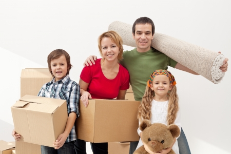 Happy family moving into a new home carrying their stuff photo