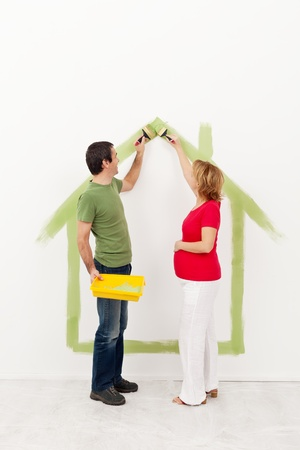 Couple expecting a baby - painting their new home Stock Photo - 17347159