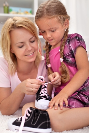 Mother teaching child how to tie shoes - showing the steps photo