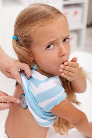 cough medicine: Coughing little girl at the doctors being checked with stethoscope Stock Photo