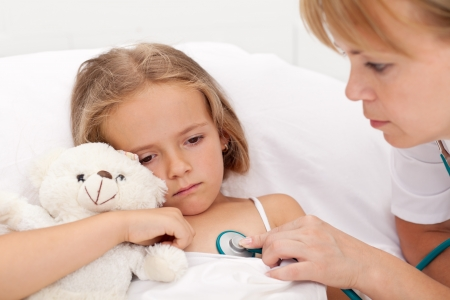 Sad little girl laying sick in bed checked by a doctor photo