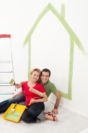 Happy couple painting in their home - sitting with utensils photo