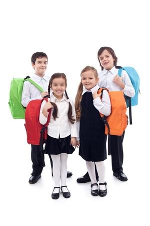 school backpack: Felices los niños escolares, niños y niñas con bolsas de colores - aislado Foto de archivo