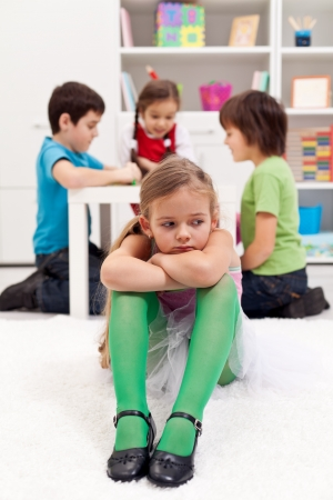 Sad little girl sitting excluded by the other kids photo
