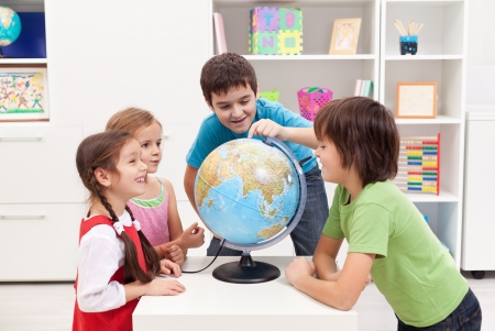 kids learning: Kids looking at earth globe and telling stories Stock Photo