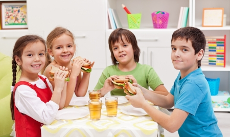 sandwich bread: Happy kids having a healthy snack in their room Stock Photo