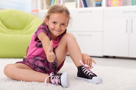 Kleines Mädchen lernen, wie sie ihre Schuhe zu binden, ist stolz auf sich