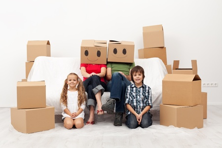 Family moving to a new home - sitting among cardboard boxes Stock Photo - 17481154