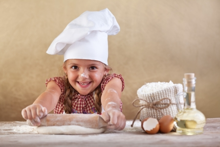 Happy little chef smeary with flour stretching the dough photo