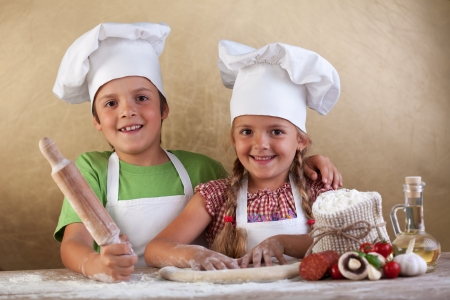 making fun: Happy kids with chef hats making pizza togheter - stretching the dough Stock Photo