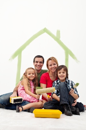 Family with two kids repainting their home concept - together holding utensils photo